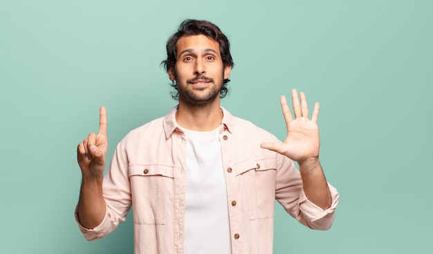 Młody przystojny indyjski mężczyzna uśmiecha się i wygląda przyjaźnie, pokazując numer sześć lub szósty z ręką do przodu, odliczając w dół