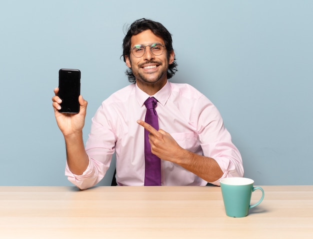 Młody przystojny indyjski mężczyzna uśmiecha się radośnie, czuje się szczęśliwy i wskazuje na bok i do góry, pokazując obiekt w przestrzeni kopii. pomysł na biznes
