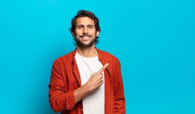 Młody przystojny indyjski mężczyzna uśmiecha się radośnie, czuje się szczęśliwy i wskazuje na bok i do góry, pokazując obiekt w przestrzeni kopii