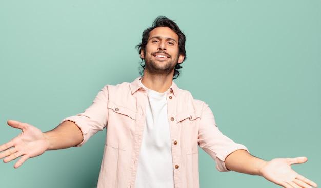 Młody przystojny indyjski mężczyzna uśmiecha się radośnie, dając ciepły, przyjazny, kochający uścisk powitalny, czując się szczęśliwy i uroczy