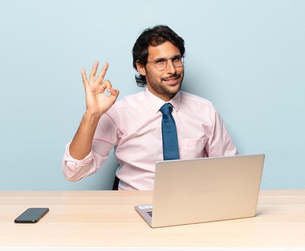 Młody przystojny indyjski mężczyzna uśmiecha się radośnie i wesoło, macha ręką, wita i wita lub żegna się. koncepcja biznesowa i frelancer
