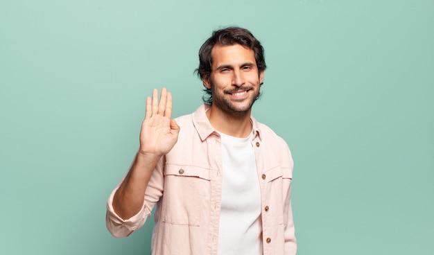 Młody przystojny indyjski mężczyzna uśmiecha się radośnie i wesoło, macha ręką, wita i wita lub żegna się