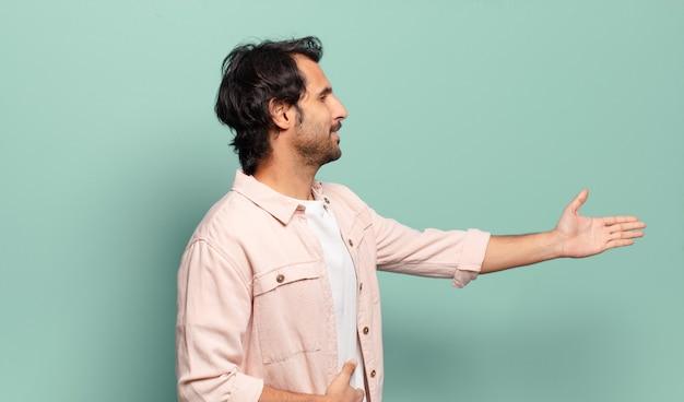 Młody przystojny indyjski mężczyzna uśmiecha się, wita i oferuje uścisk dłoni, aby zamknąć udaną transakcję, koncepcja współpracy