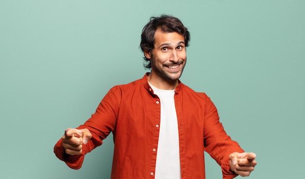 Młody przystojny indyjski mężczyzna uśmiecha się z pozytywnym, udanym, szczęśliwym nastawieniem, wskazując na aparat, robiąc znak pistoletu rękami