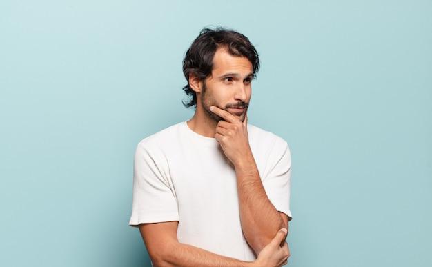 Młody przystojny indyjski mężczyzna uśmiecha się z radosnym, pewnym siebie wyrazem z ręką na brodzie, zastanawia się i patrzy w bok