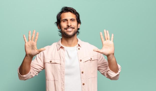 Młody przystojny indyjski mężczyzna uśmiechający się i wyglądający przyjaźnie, pokazujący liczbę dziesięć lub dziesiątą ręką do przodu, odliczając w dół