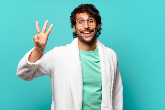 Młody przystojny indyjski mężczyzna uśmiechający się i wyglądający przyjaźnie