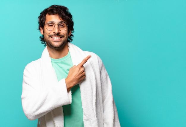 Młody przystojny indyjski mężczyzna uśmiechający się radośnie, czujący się szczęśliwy i wskazujący na bok i do góry, pokazujący obiekt w przestrzeni kopii i noszący szlafrok
