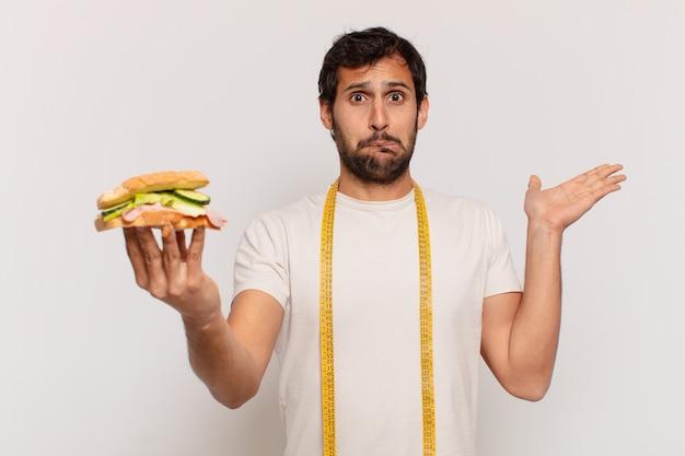 Młody przystojny indyjski mężczyzna wątpiący lub niepewny wyraz twarzy i trzymający kanapkę