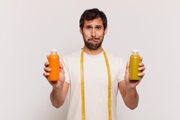 Młody przystojny indyjski mężczyzna wątpiący lub niepewny wyraz twarzy i trzymający koktajl