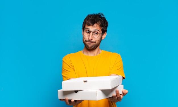 Młody przystojny indyjski mężczyzna wątpiący lub niepewny wyraz twarzy i trzymający pizze na wynos