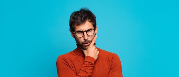 Młody przystojny indyjski mężczyzna wątpiący lub niepewny wyraz twarzy
