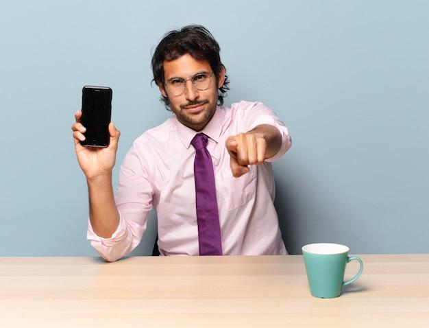 Młody przystojny indyjski mężczyzna, wskazując na aparat z zadowolonym, pewnym siebie, przyjaznym uśmiechem, wybiera cię. pomysł na biznes