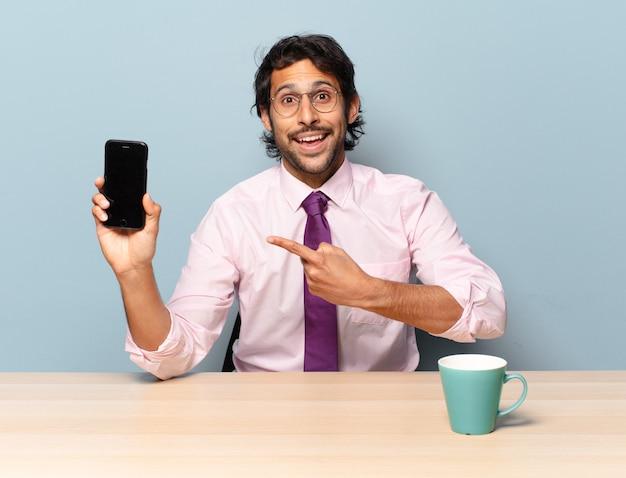 Młody przystojny indyjski mężczyzna wygląda podekscytowany i zaskoczony, wskazując na bok i do góry, aby skopiować miejsce. pomysł na biznes