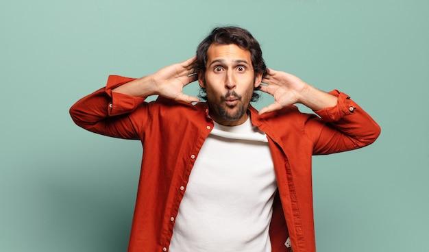 Młody przystojny indyjski mężczyzna wyglądający na podekscytowanego i zaskoczonego, z otwartymi ustami, z obiema rękami na głowie, czujący się jak szczęśliwy zwycięzca