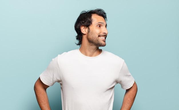 Młody przystojny indyjski mężczyzna wyglądający na szczęśliwego, wesołego i pewnego siebie, uśmiechającego się dumnie i patrząc na bok z obiema rękami na biodrach