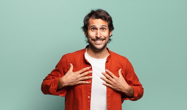 Młody przystojny indyjski mężczyzna wyglądający na szczęśliwego, zaskoczonego, dumnego i podekscytowanego, wskazując na siebie