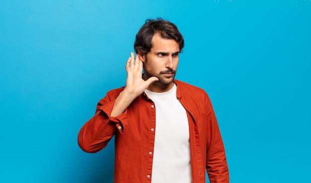 Młody przystojny indyjski mężczyzna wyglądający poważnie i zaciekawiony, słuchający, próbujący usłyszeć tajną rozmowę lub plotkę, podsłuchujący