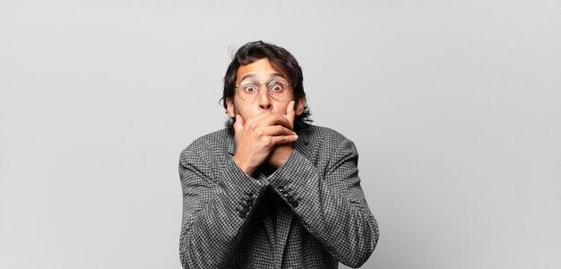 Młody przystojny indyjski mężczyzna zakrywający usta dłońmi w szoku