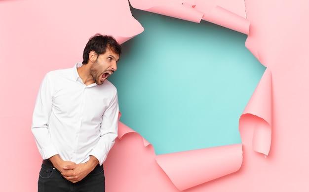 Młody przystojny indyjski mężczyzna zły wyraz na tle złamanej dziury papieru