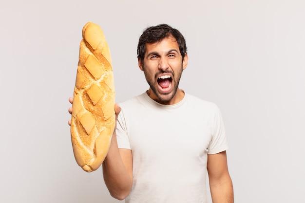 Młody przystojny indyjski mężczyzna zły wyraz twarzy i trzymający chleb