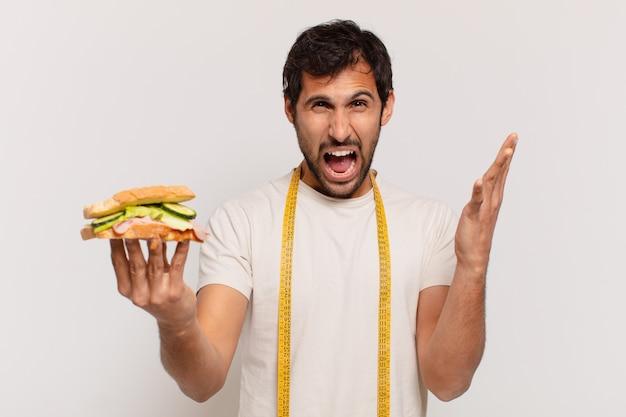 Młody przystojny indyjski mężczyzna zły wyraz twarzy i trzymający kanapkę