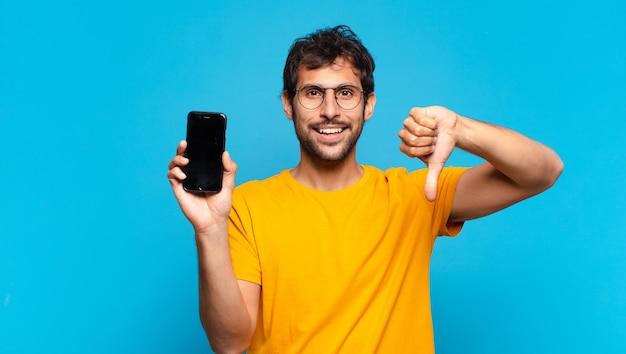 Młody przystojny indyjski mężczyzna zły wyraz twarzy i trzymający telefon komórkowy