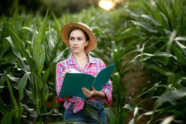 Młody przystojny inżynier rolnictwa stojący w polu kukurydzy z tabletem na początku lata.