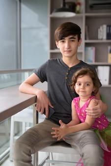 Młody przystojny irański nastolatek z młodszą siostrą relaks w domu