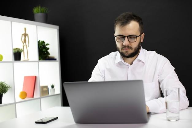 Młody przystojny it profesjonalny freelancer pracuje nad projektem w domu