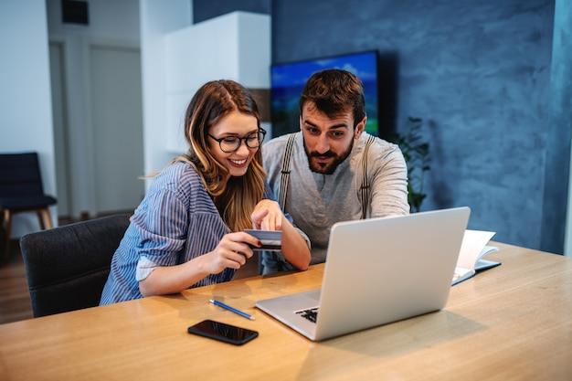 Młody przystojny kaukaski brodaty uśmiechnięty mężczyzna mówi o rzeczach, które chcą kupić online. kobieta trzyma i wskazuje przy kredytową kartą. na stole jest laptop.