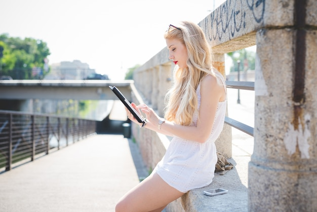 Młody przystojny kaukaski długie blond włosy proste kobieta za pomocą urządzeń technologicznych