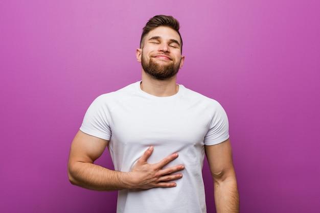 Młody przystojny kaukaski mężczyzna dotyka brzucha, uśmiecha się delikatnie, jedzenie i koncepcja satysfakcji.