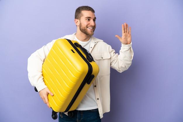 Młody przystojny kaukaski mężczyzna na białym tle na fioletowej ścianie w wakacje z walizką podróżną i pozdrawiając