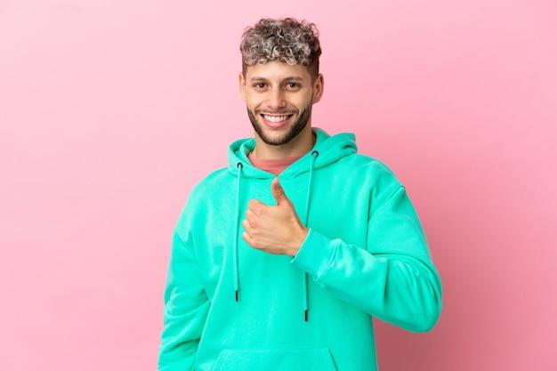 Młody przystojny kaukaski mężczyzna na białym tle na różowym tle dający gest kciuka w górę