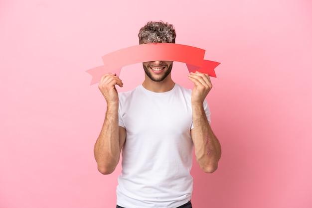 Młody przystojny kaukaski mężczyzna na białym tle na różowym tle trzyma pustą tabliczkę i chowa się za nią