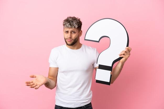 Młody przystojny kaukaski mężczyzna na białym tle na różowym tle, trzymający ikonę znaku zapytania i mający wątpliwości