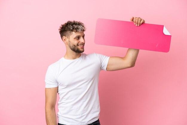Młody przystojny kaukaski mężczyzna na białym tle na różowym tle trzymający pustą afisz