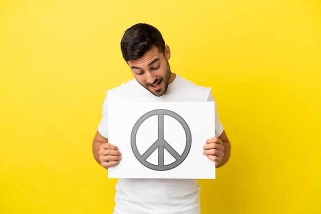 Młody przystojny kaukaski mężczyzna na białym tle na żółtym tle trzyma afisz z symbolem pokoju
