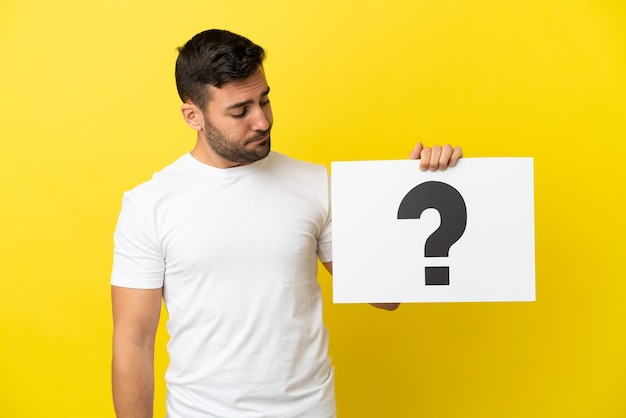 Młody przystojny kaukaski mężczyzna na białym tle na żółtym tle trzyma afisz z symbolem znaku zapytania