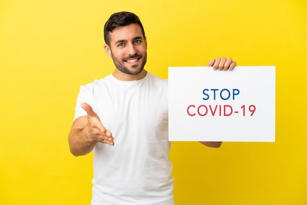 Młody przystojny kaukaski mężczyzna na białym tle na żółtym tle trzyma afisz z tekstem stop covid 19 robienie transakcji