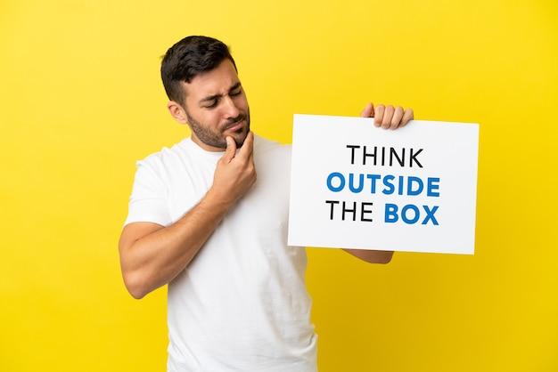 Młody przystojny kaukaski mężczyzna na białym tle na żółtym tle trzyma afisz z tekstem think outside the box and thinking