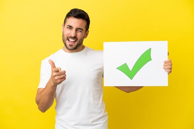 Młody przystojny kaukaski mężczyzna na białym tle na żółtym tle, trzymając afisz z tekstem zielona ikona znacznika wyboru i wskazująca do przodu