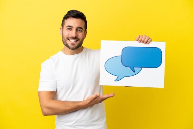 Młody przystojny kaukaski mężczyzna na białym tle na żółtym tle trzymający afisz z ikoną dymka z radosnym wyrazem twarzy