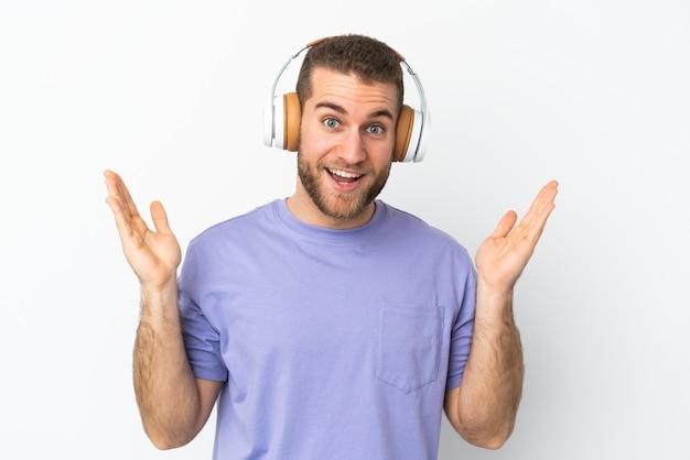 Młody przystojny kaukaski mężczyzna na białym tle zaskoczony i słuchający muzyki