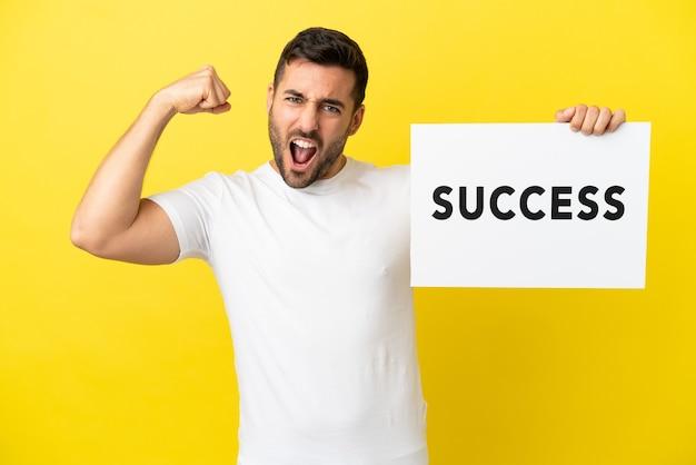 Młody przystojny kaukaski mężczyzna na żółtym tle trzyma afisz z tekstem sukces i robi silny gest