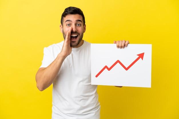 Młody przystojny kaukaski mężczyzna na żółtym tle trzyma znak z rosnącym symbolem strzałki statystyk i krzyczy