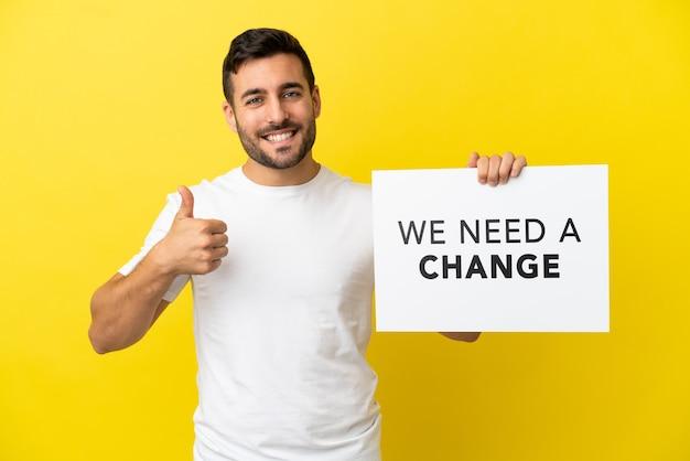 Młody przystojny kaukaski mężczyzna na żółtym tle trzymający tabliczkę z tekstem potrzebujemy zmiany z kciukiem do góry
