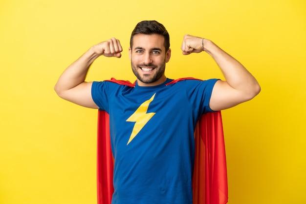Młody przystojny kaukaski mężczyzna na żółtym tle w kostiumie superbohatera i robi silny gest