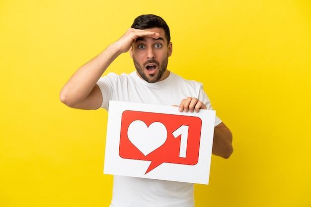 Młody przystojny kaukaski mężczyzna odizolowany na żółtym tle trzymający afisz z ikoną like ze zdziwionym wyrazem twarzy